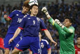 HEROIC SAVE: Singapore's goalkeeper Izwan Mahbud (right) fighting for the ball with Japan's Shinji Okazaki (centre) and Yuya Osako during the 2018 World Cup qualifying soccer match at Saitama Stadium.