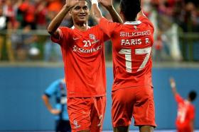 BACK ON SONG: Safuwan Baharudin (left, celebrating with Faris Ramli) after scoring a crucial goal by switching from defence to attack.