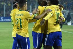 TEAM SPIRIT: Willian is mobbed by Brazil teammates (from far left) Filipe Luis, Philippe Coutinho and Roberto Firmino for his star turn against Venezuela.