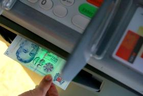 File photo of a person drawing money from an ATM.