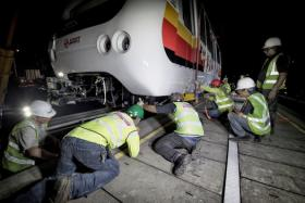 SMRT workers lifting the new train-cars for the Bukit Panjang LRT system, which will progressively go into service from the last quarter of 2014. This will boost the number of trains and help ease crowding during peak hours.