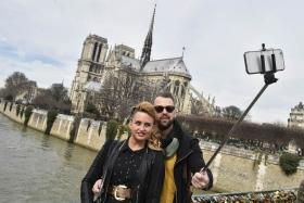Tourists using a selfie stick to take a picture of themselves near the Notre Dame cathedral in Paris. Disney on June 26, 2015 became the latest major tourism operator to ban selfie sticks as part of a growing backlash against the extendable devices.
