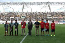 MEMORABLE EXPERIENCE: (Above, from left) NFA U-14s boys Elijah Lim, Nur Adam Abdullah and Hamizan Hisham exchanging pennants with their Matsumoto Yamaga counterparts and engaging in volunteer work before last Saturday's J-League game at the Alwin Stadium.