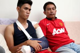GRIEVING: Azreen Sairudin and his father Sairudin Sani, who is wearing the Manchester United jersey Aqil gave him for his birthday in December.
