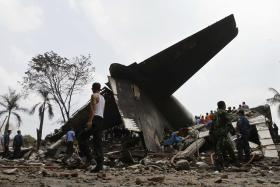Security forces and rescue teams examine the the wreckage of an Indonesian military C-130 Hercules transport plane after it crashed into a residential area in the North Sumatra city of Medan, Indonesia,