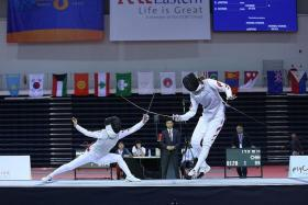 TAKE THAT: South Korea's Lim Seung Min (left) striking towards China's Gong Yu in the women's team foil final at the OCBC Arena.