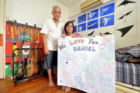 MEMORIES: Mr Daniel Tan's parents holding up the tribute made by his friends that was displayed during his funeral wake last week.