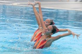 STRIKE A POSE: Synchronised swimmers Carolyn Rayna Buckle (front) and Miya Yong Hsing competing in the duet category at the National Schools Synchronised Swimming Championships.