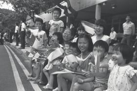 Madam Yeo Soo Hoon, and her 12 grandchildren watching the National Day Parade in 1985