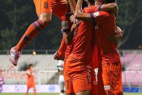 CHEERS, MATE: Atsushi Kawata (with orange boots) hugs Fumiya Kogure (yellow boots) after the latter assists him for the opening goal.