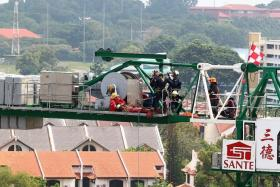 AID: SCDF officers securing the injured worker to a stretcher before lowering him safely to the ground. The 22-year-old maintenance mechanic had a deep cut on his right leg.
