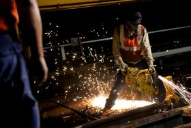 A member of SMRT's Track Renewal Team operates a rail cutter to slice through the tracks.