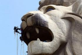 HOT SHOWER: Members of the eight-man abseiling cleaning crew, hired by German firm Kärcher, taking on the mammoth task of cleaning the Merlion on Sentosa, using hot water.