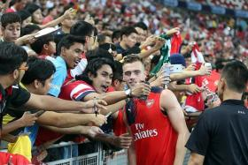 PRIZED CATCH: Fans clamouring to take selfies and obtain autographs with Arsenal stars like Calum Chambers (left) after their training session, led by team manager Arsene Wenger yesterday.