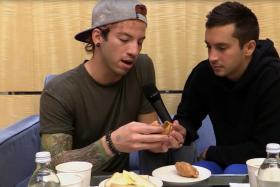 Josh Dun (left) and Tyler Joseph from Twenty One Pilots examine a curry puff.