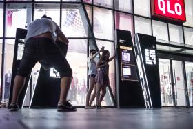 People get into suggestive pose in front of a Uniqlo clothes store in Beijing, after a sex tape purportedly shot in a fitting room of the clothing chain went viral.
