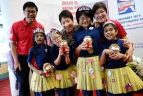 CHARITY: From left, Dr Khoo Kah Siang, CEO (Singapore), Great Eastern Life, Minister in the Prime Minister's Office Grace Fu and CEO, Great Eastern Financial Advisers Jesslyn Tan with girls from Lee Kong Chian MINDS Gardens School in their yellow tutus which cost $5 apiece.