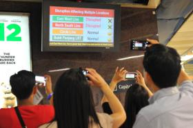 Commuters take photos of a signboard at City Hall MRT station after train services on the East-West and North South lines were disrupted on July 7 - the first time both lines were entirely down.