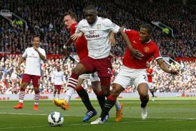 BATTERING RAM: Christian Benteke holding off the challenges of Manchester United's Phil Jones (left) and Antonio Valencia (right) in an EPL game in April.Benteke scored but Villa lost 3-1.