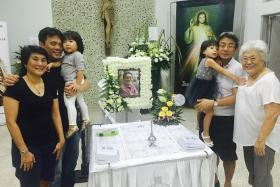 LOVED ONES BID FAREWELL: Quah Kim Swee's family - (from left) daughter Bee Jin, youngest son Soon Aun with baby, eldest son Soon Hong with child, and wife Helen - at the wake held at St Joseph's Church.