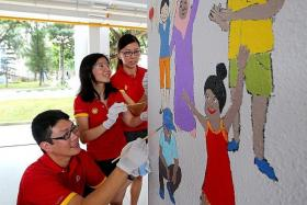 COLLABORATE: Mr Jonathan Ng, Madam Dwen Hwee, and Ms Liew Bee Ling (from left to right) working on a mural that depicts people of different races celebrating Hari Raya. They, along with three other Shell volunteers, finished one side of the pillar in two hours.