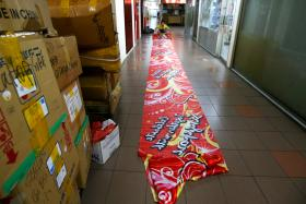 BOOM TIMES: A Singapore-themed banner being rolled up at R A International Marketing.