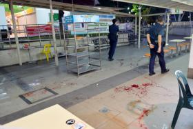 Police at the area in Bedok North hawker centre which they cordoned off, after a parang attack on  July 21.
