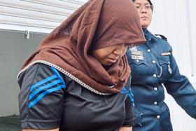 Nor Nazierah Rahmat, 26, being escorted out of court by a police officer after being charged with her child's murder.