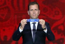 "Former German soccer player Bierhoff holds up the slip showing ""England"" during the preliminary draw for the 2018 FIFA World Cup"