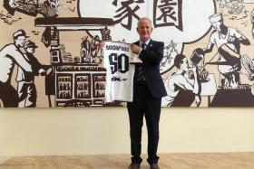 FOR SINGAPORE: Valencia's commercial and marketing director Peter Draper, posing with a commemorative Valencia jersey at the Ritz-Carlton Millenia yesterday, hopes a Singapore footballer will 