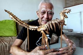 FOR HIS SON: Mr Chan with the dinosaur skeleton origami he folded with three others as a gift to his son more than five years ago.
