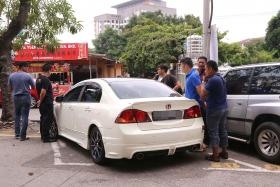 CAUGHT: Malaysian police officers arrest the man (circled) who is believed to have stolen Mr Joe Ong's Honda Civic.
