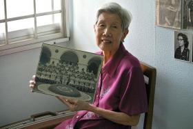 MEMORIES: Ms Rosalind Tan with a photo of the eighth batch of female police officers at the Police Training School in 1951.