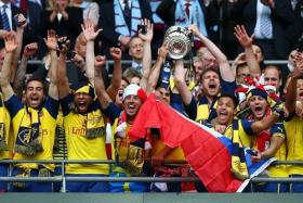 GUNNER BE US: Emmanuel Petit believes that the Gunners' successful FA Cup defence in May (above) augurs well for an EPL title tilt.