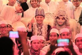 Singapore Idol Hady Mirza and his bride, Ms Nurjannah Nur Wahid pose for their wedding last year: More people got married in 2014 compared to 2013 - and they are also marrying later in life.
