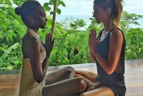 BOOB JOB: Supermodel Gisele Bundchen has become a laughing stock among fellow Brazilians for an apparent boob job. She is pictured above, on the right, in a yoga pose on Instagram with model Kiara Kabukuru (left).
