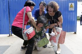 One of the relatives onboard Malaysia Airlines flight MH370, kneels down in front of media before she and other family members express their demands to Malaysia Airlines outside its Beijing office on August 6, 2015.