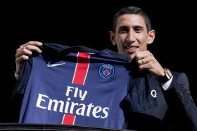 Paris Saint-Germain's new Argentinian midfielder Angel Di Maria poses with his PSG jersey on a balcony during his official presentation in Paris on August 6, 2015.