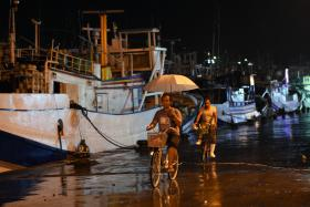 Workers riding past fishing boats moored in a shelter at Nanfangao harbour in Yilan as typhoon Soudelor approaches eastern Taiwan