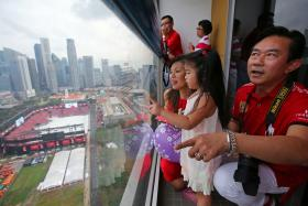 PROUD: Mr Pach Ang watching the parade with his daughter Sephina and wife, Vivien.