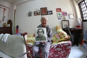 A LIFETIME OF MEMORIES: Madam Lim Beak holding an old photo of herself.
