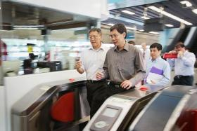 ON THE GROUND: Mr Lui Tuck Yew (right, in darker shirt) pictured here at Clementi MRT station.