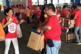 FREE: A promoter distributing free TNP print copies and digital access cards in the TNP bags at the Marina Bay Floating Platform on Aug 9.