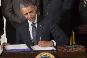 US president Barack Obama uses his favoured left hand to sign the  H.R. 1295 Trade Preferences Extension Act of 2015 two months ago.