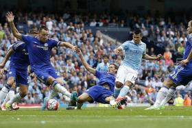 CITY'S OPENER: Man City's Sergio Aguero scoring the first goal despite the attention of Chelsea's entire defence.