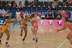 FINAL FLOURISH: Singapore's Kimberly Lim (right) picks up a pass in the Republic's 59-32 victory over Sri Lanka in the Netball World Cup 15th/16th classification match yesterday.