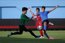 BATTLE: Singapore Under-16's Ikhsan Fandi (in blue) attempting to score against their U-15 counterparts as they fight for third place.