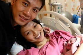 Qi Yuwu (left) with wife Joanne Peh and their newborn daughter.