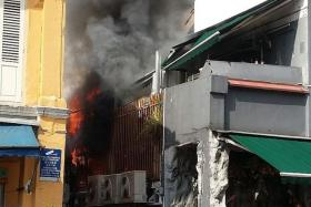 SMOKE: A crowd gathering outside Jungle Tandoor Restaurant as the fire burns on the second floor.