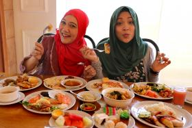 TUCKING IN: Local actresses Mastura Ahmad (left) and Syirah Jusni having lunch at Asian Market Cafe at Fairmont Singapore.